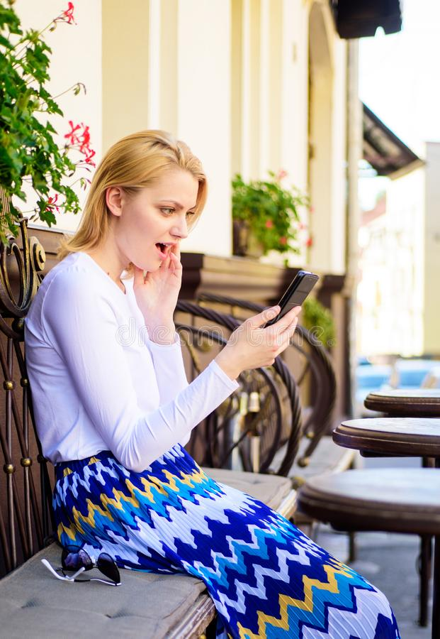Shocking content. Girl communicating with friend using smartphone. Woman surprised face surfing internet smartphone cafe royalty free stock photography