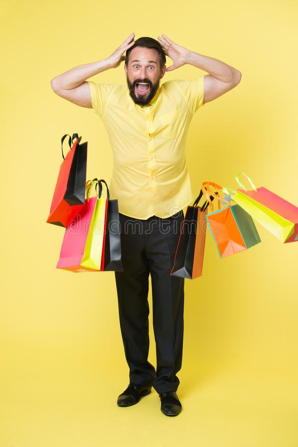 Shocking discount. Man shouting face dropping shopping bags. Guy shocked surprised face dropped bunch bags. Total sale stock images
