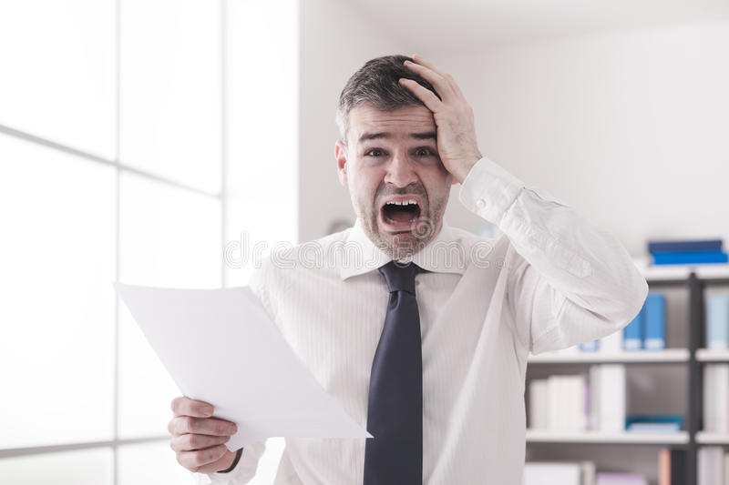 Shocking expensive bills. Businessman in the office receiving shocking bills and tax documents, he is gasping and screaming stock photography