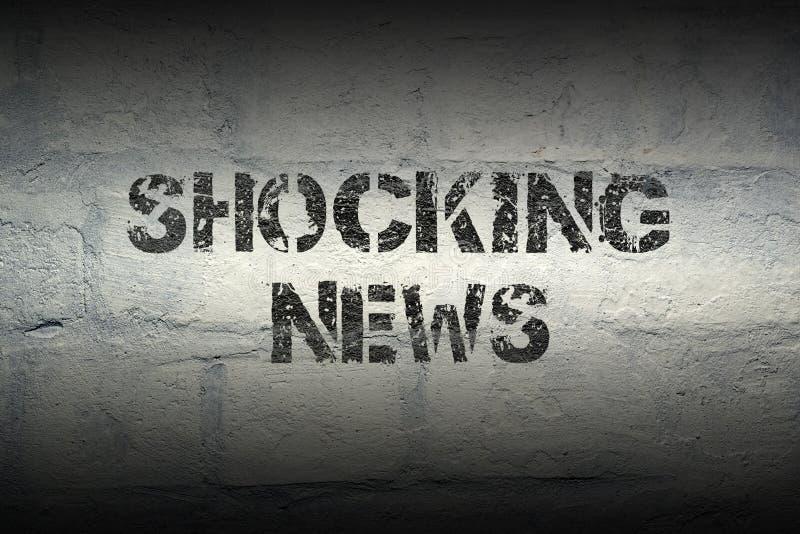 Shocking news GR. Shocking news stencil print on the grunge white brick wall stock images