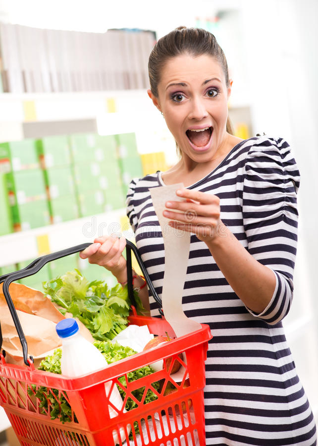 Shocking prices at supermarket. Astonished young woman with full shopping basket checking a grocery receipt stock photos