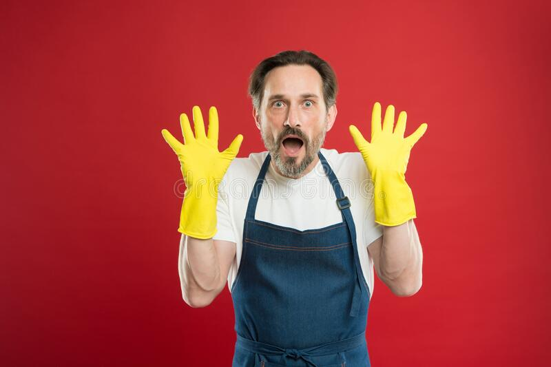 Shocking results. On guard of cleanliness. Cleaning service and household duty. Lot of work. Man in apron with gloves. Cleaning. Cleaning day today. Bearded guy royalty free stock photo