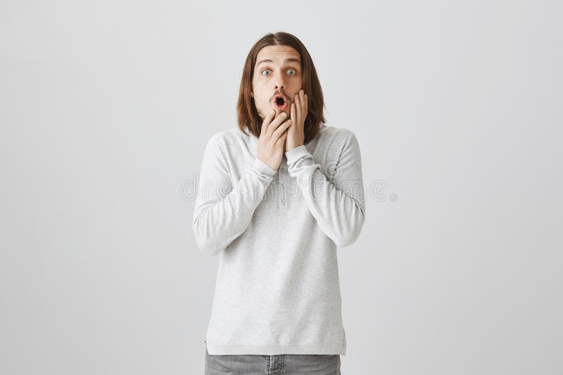 Shocking revelation been made. Studio shot of emotive surprised attractive guy with long brown hair and beard saying wow stock photos