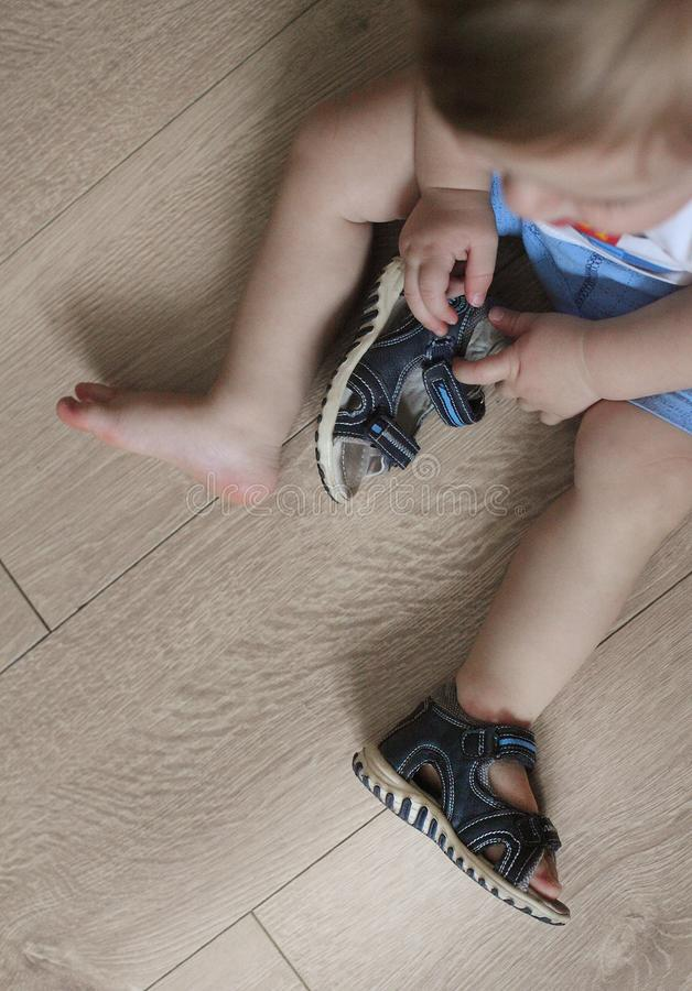 Shod legs of the baby. Children`s sandals on their feet. Toddler shoes. Tourist sandals for the smallest travelers. A new purchase. In a shoe store stock images
