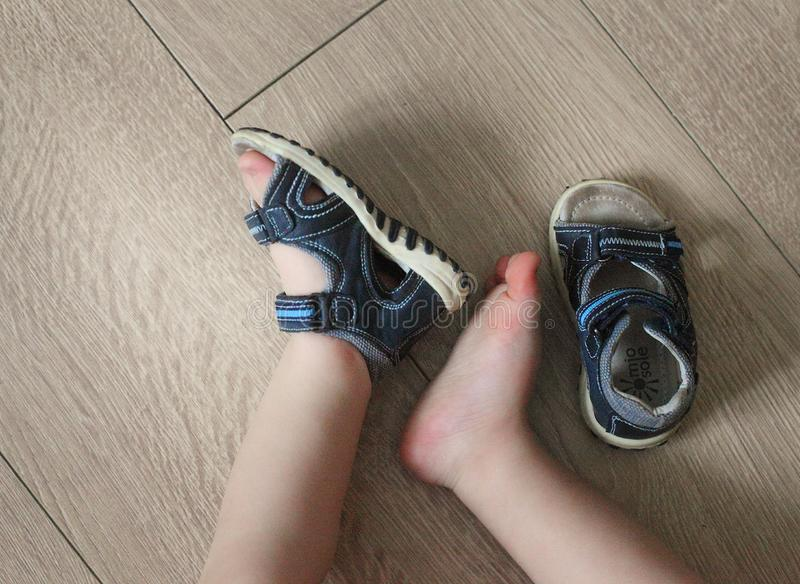 Shod legs of the baby. Children`s sandals on their feet. Toddler shoes. Tourist sandals for the smallest travelers. A new purchase. In a shoe store stock photo