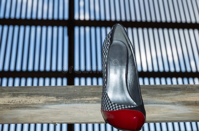 Shoe with a combination of colors red, black and white on a wooden ledge. With a large window of grid in the background royalty free stock photography