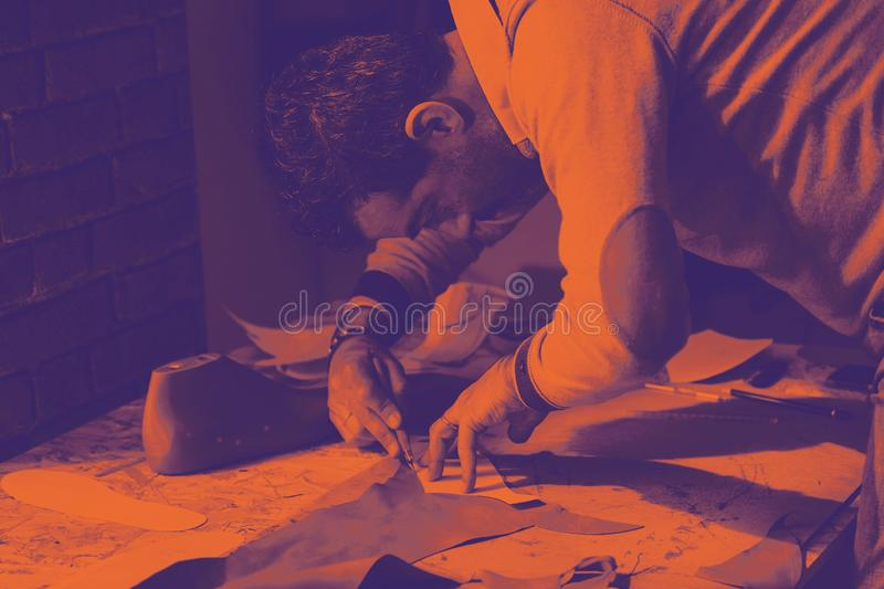 Shoe designer working with leather. Bitonal Effect. Shoemaker or shoe designer working with leather for the production of handmade shoes. Bitonal effect with two royalty free stock images