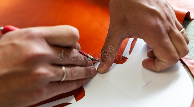 Shoe designer working with leather. Shoemaker or shoe designer working with leather for the production of handmade shoes stock photo