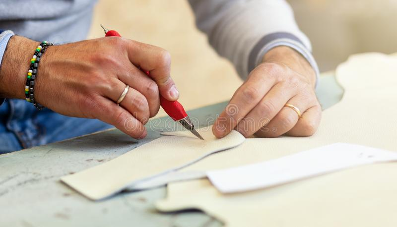 Shoe designer working with leather. Shoemaker or shoe designer working with leather for the production of handmade shoes royalty free stock images