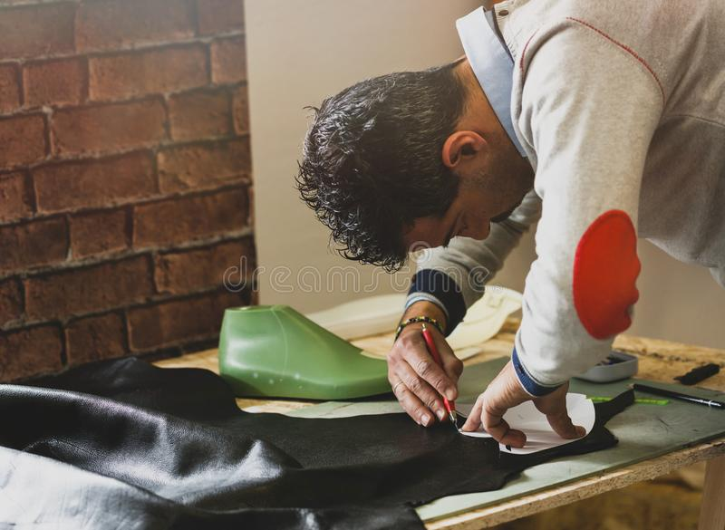 Shoe designer working with leather. Shoemaker or shoe designer working with leather for the production of handmade shoes stock photography