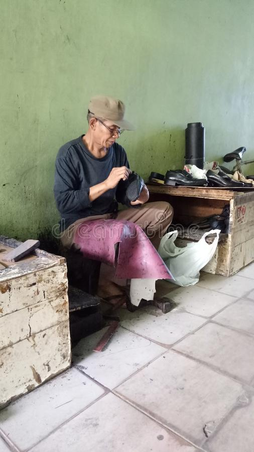 The shoe fixer. A rare profession hardworker royalty free stock photography