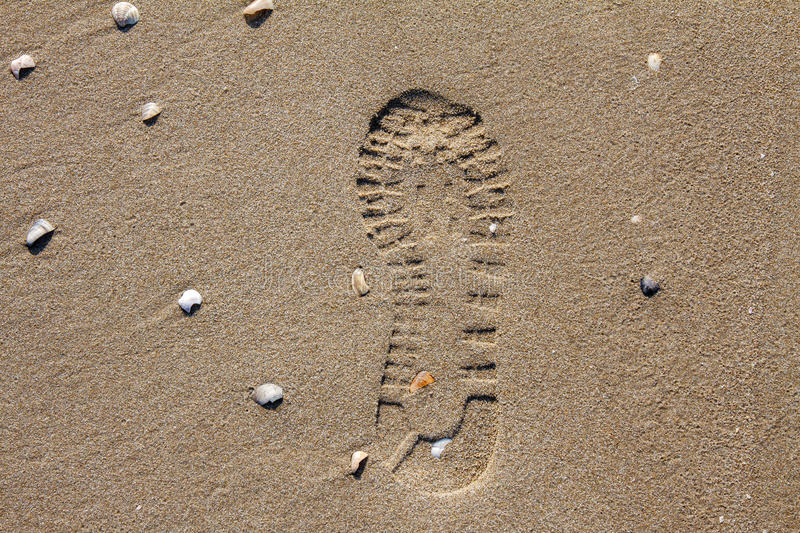 Shoe imprint in the sand of a beach royalty free stock images
