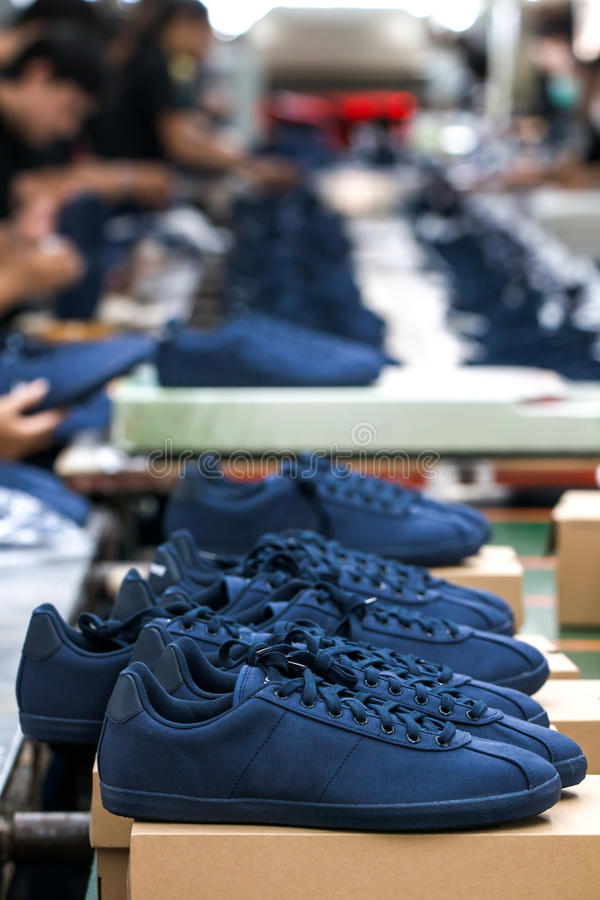 Shoe making factory. Worker making shoes in production line conveyor royalty free stock photography