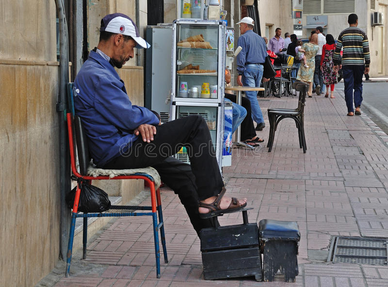 Shoe-shiner man in North Africa stock photo