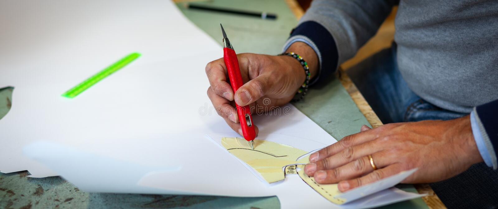 Shoe designer working with paper models for leather cutting. Shoemaker or shoe designer working with lwith paper models for leather cutting royalty free stock photos