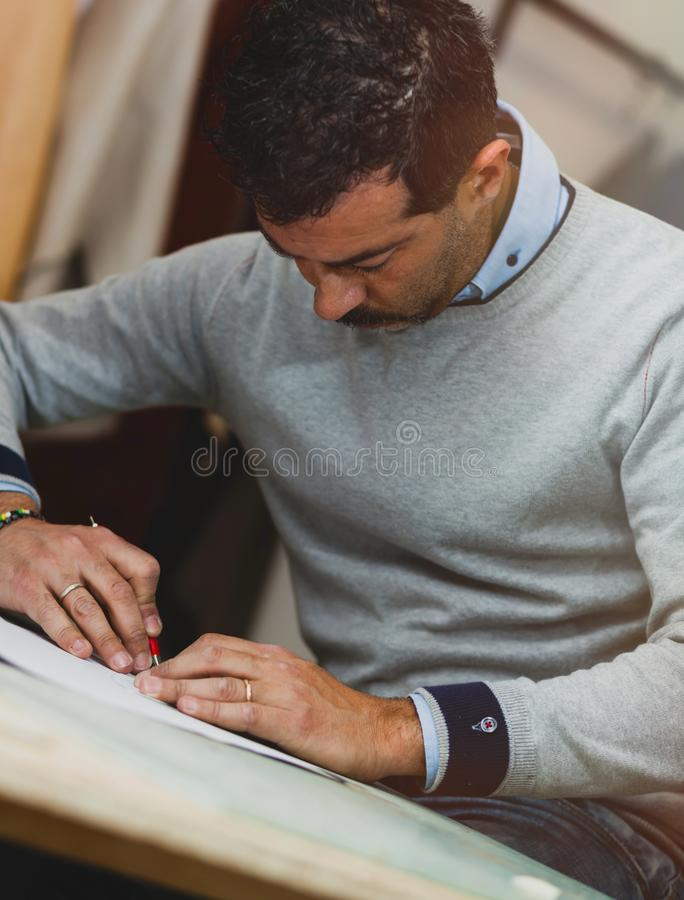 Shoe designer working with paper models for leather cutting. Shoemaker or shoe designer working with lwith paper models for leather cutting stock photography