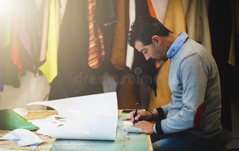 Shoe designer working with paper models for leather cutting. Shoemaker or shoe designer working with lwith paper models for leather cutting stock image