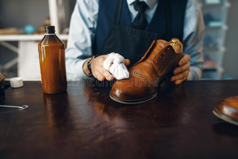 Shoemaker wipes black shoe polish, footwear repair. Service. Craftsman skill, shoemaking workshop, master works with boots, cobbler shop royalty free stock photos
