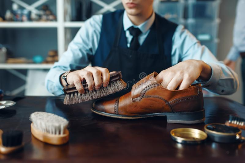Shoemaker wipes black shoe polish, footwear repair. Service. Craftsman skill, shoemaking workshop, master works with boots, cobbler shop stock images