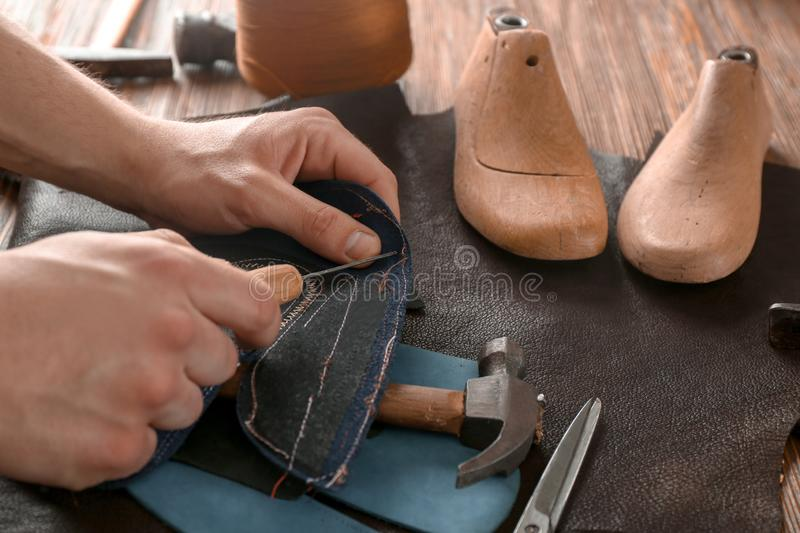Shoemaker working with leather at factory royalty free stock images