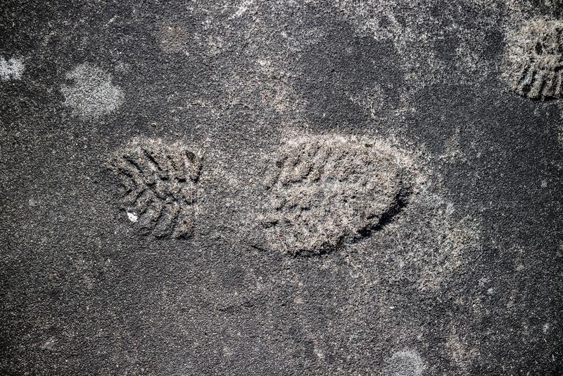 Shoeprint op grijs asfalt wordt gestempeld dat stock foto