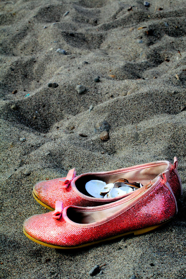 Shoes on the beach. A little girls pink shoes as container for collected shells at the beach. Possible background for flier or brochure royalty free stock images