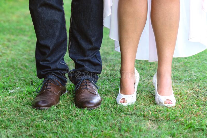 Shoes of the bride and groom standing next to the green grass. Brown shoes of the groom. white shoes bride stock photography