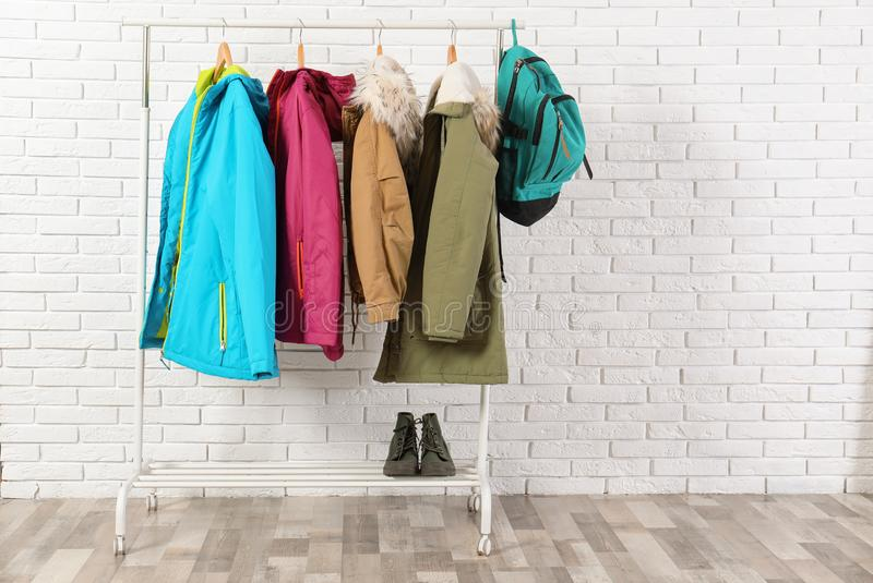 Shoes and clothes on hanger stand against wall. Idea for interior decor. Shoes and clothes on hanger stand against brick wall. Idea for interior decor royalty free stock photography