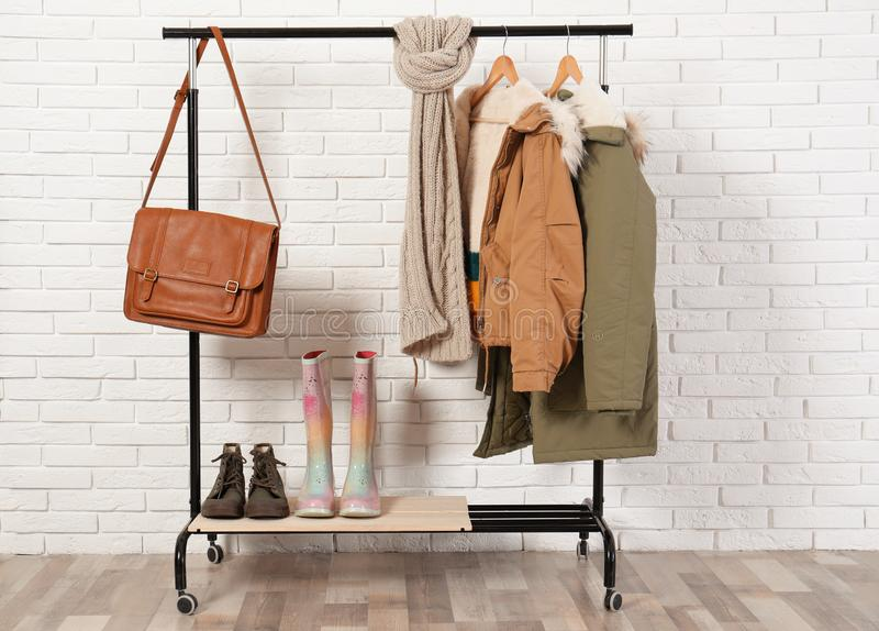 Shoes and clothes on hanger stand against wall. Idea for interior decor. Shoes and clothes on hanger stand against brick wall. Idea for interior decor royalty free stock image