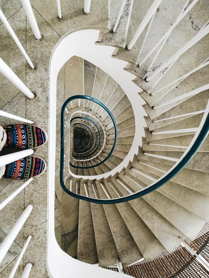 Shoes with colorful pattern on swirling downwards staircases stock image