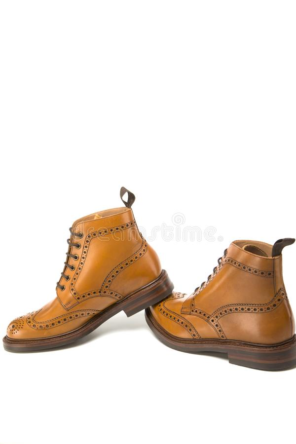 Shoes Concepts. Premium Tanned Brogue Derby Boots of Calf Leather with Rubber Sole. Isolated Over Pure White. Shoes Placed in Lin. E. Vertical Image stock photography
