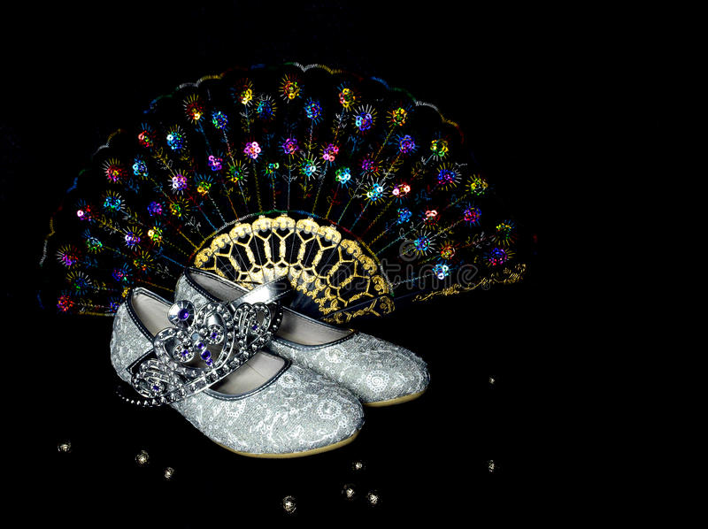 Shoes, crown and fan for the little girl. Little princess attire. Shoes, crown and fan for the little girl princess royalty free stock photo