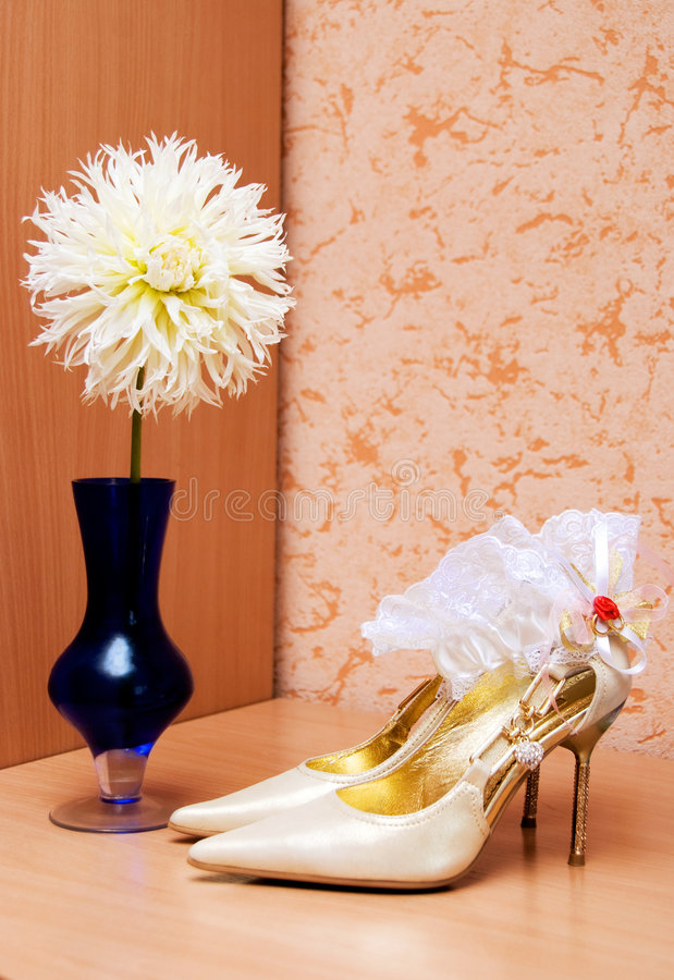Shoes and garter on the table. Shoes and garter of a bride on the table stock photography