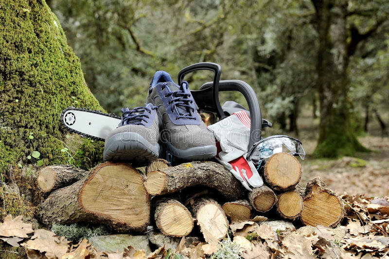 Shoes, gloves and safety goggles for safe use of a chainsaw. royalty free stock photography