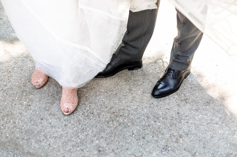 The shoes of a groom and a bride standing together royalty free stock photo