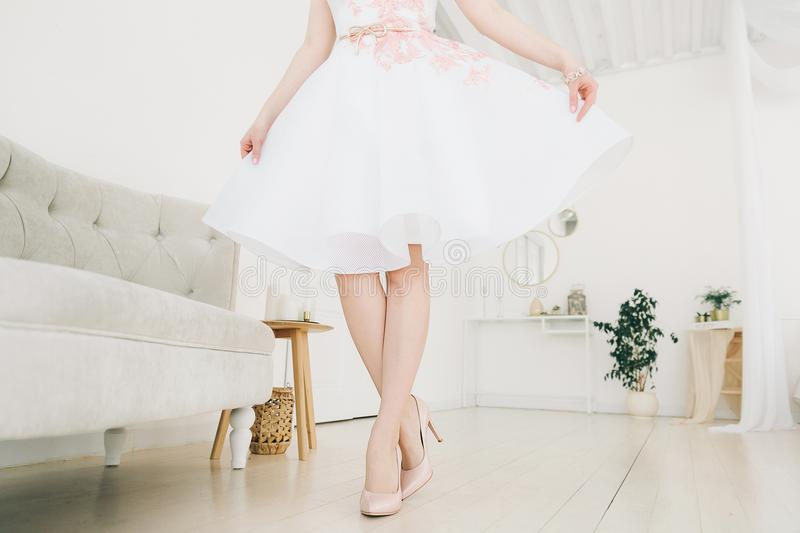 Shoes on the legs of a girl in a white dress. stock photos