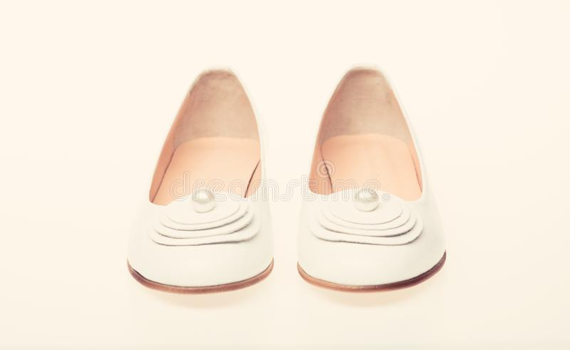 Shoes made out of white leather on white background, isolated. Footwear for women on flat sole with pearl bead as decor. Minimalism concept. Pair of royalty free stock photo