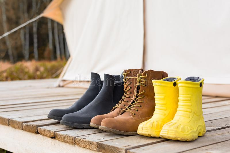 Three pair of shoes near a canvas tent stock photography