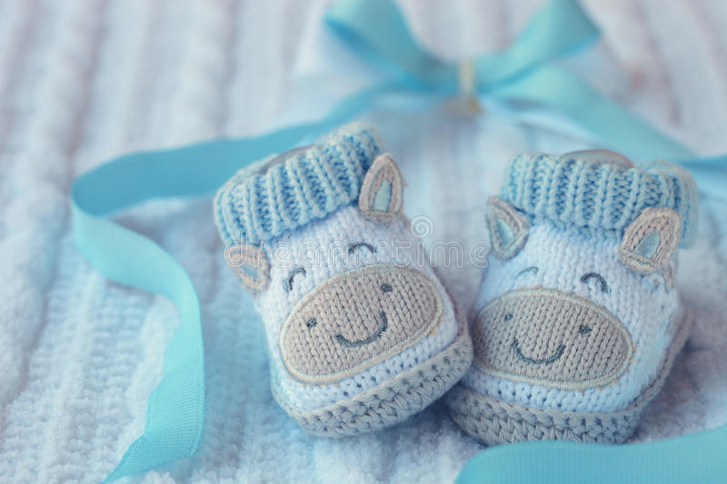Shoes for newly born baby boy. Knitted baby shoes for boy on a blue background. Greeting card stock images