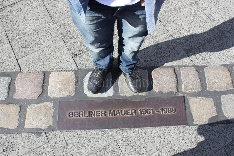 Shoes on the old berlin wall border. Man standing on the old border between east berlin and west berlin. The wall lasted from 1961 till 1989. He wears a jeans royalty free stock images
