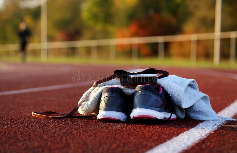 Shoes and parts of women on athletic track. At afternoon stock photography