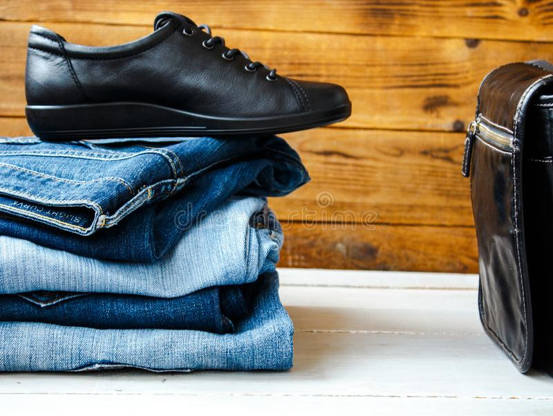 A shoes on a pile of jeans and bag stock photos