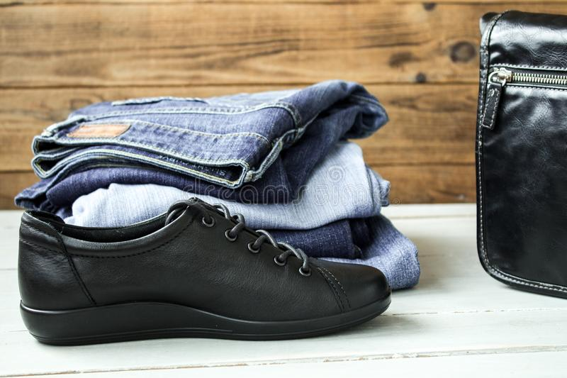 A shoes and pile of jeans and bag on a wooden background stock image