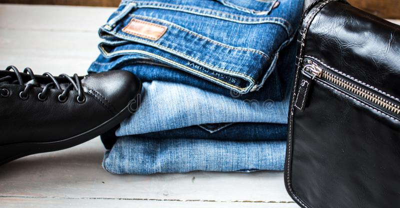 Shoes and pile of jeans and bag on a wooden background royalty free stock photo