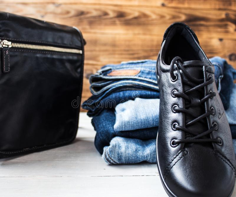 Shoes on a pile of jeans and bag on a wooden background stock photos