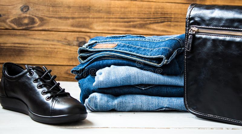 Shoes and pile of jeans and bag on a wooden background stock image