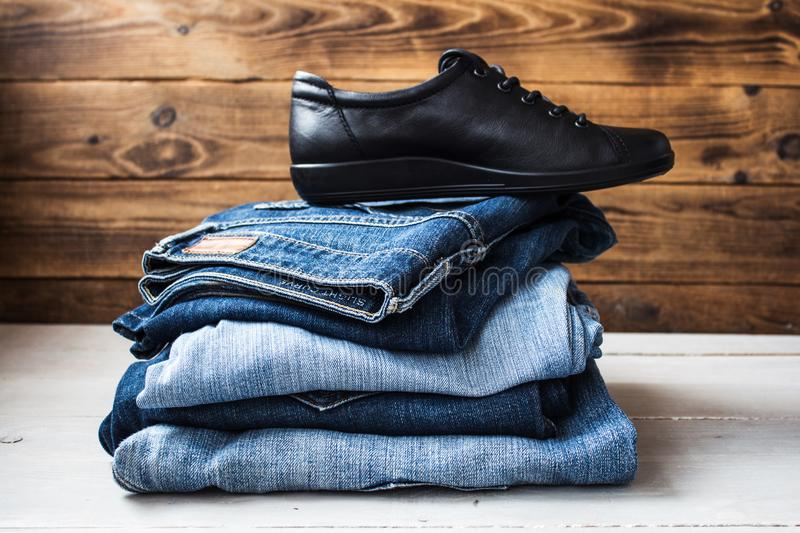 Shoes on a pile of jeans on a wooden background stock photography