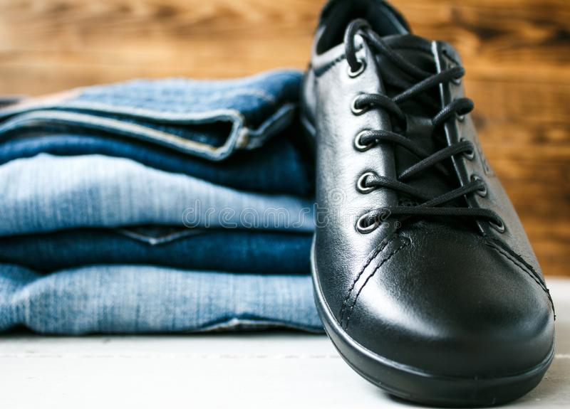 Shoes on a pile of jeans on a wooden background stock images