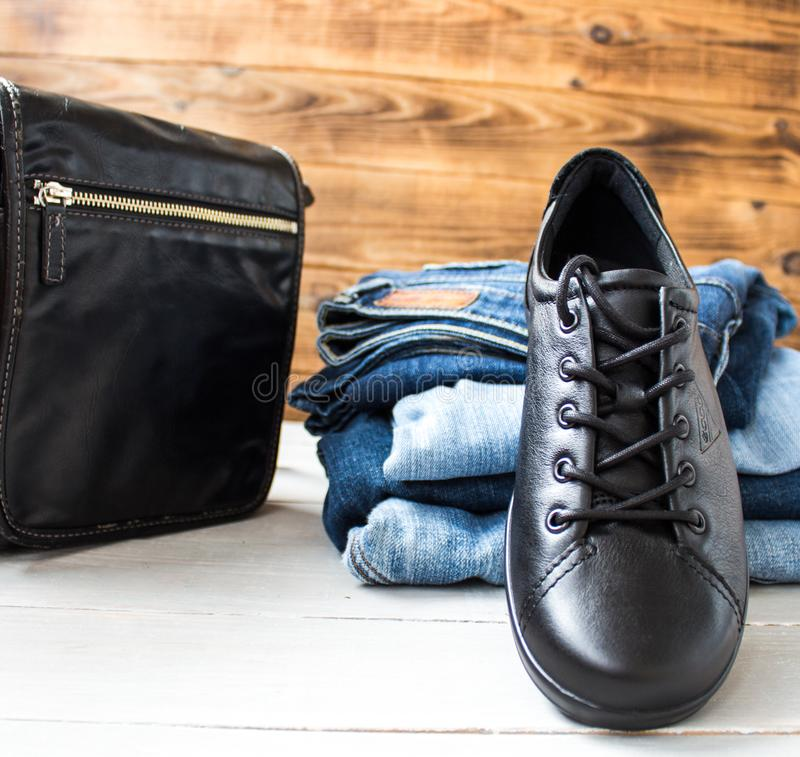 A shoes on a pile of jeans and bag on a wooden background stock photography