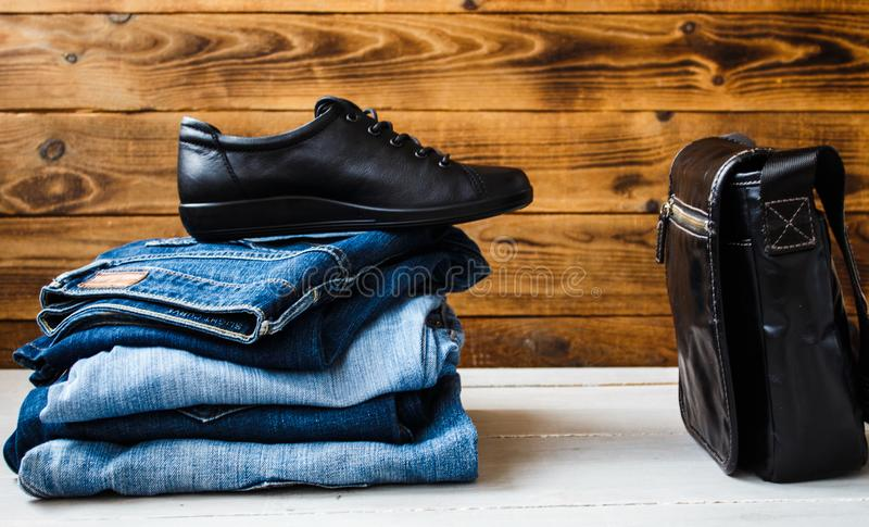 Shoes on a pile of jeans and bag on a wooden background royalty free stock photo